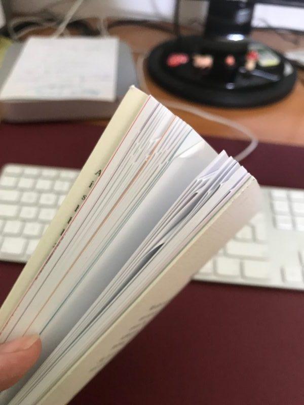 Achtsames Schreiben, Seitenansicht des Buches mit Seiten und Eselsohren, Appel-Tastatur im Hintergrund