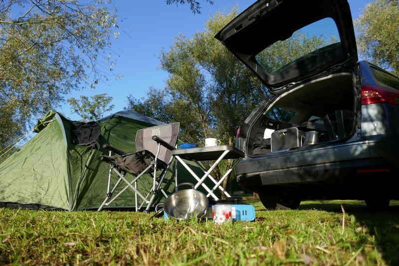 Zelt, Campingsessel und Kombi PKW mit geöffneter Heckklappe, Frühstück am Campingplatz