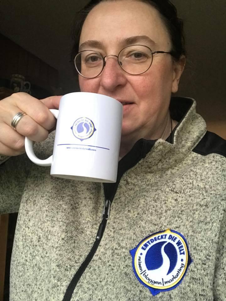 Angelika Wohofsky, Frau mit Strickjacke und Entdeckt die Welt Logo trinkt Kaffee aus einer weißen Tasse mit Logo Aufdruck