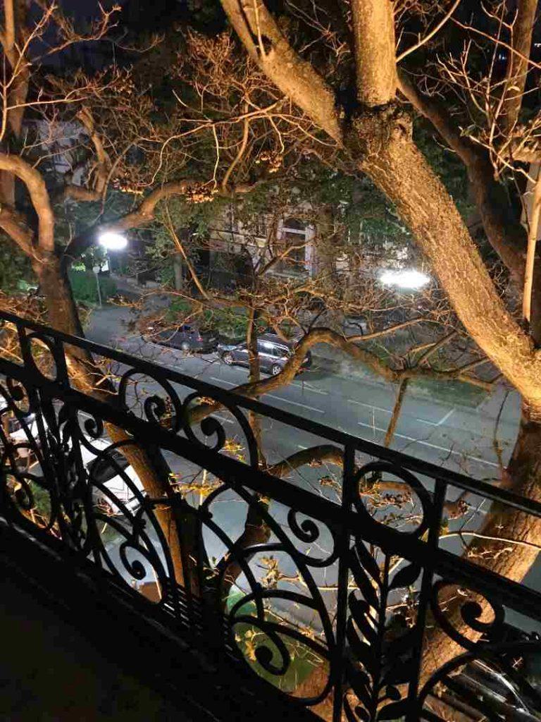 Balkon, davor stehen Bäume und unten auf der Straße stehen zwei Autos